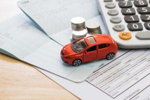 franquia concessionária: miniatura de carro apoiado em papeis com moedas e calculadora