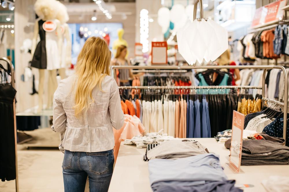 moça olhando roupas em loja ilustrativo texto