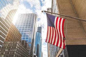 franquias brasileiras no exterior: bandeira dos estados unidos entre grandes prédios comerciais