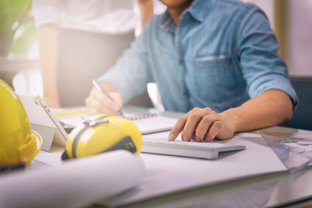 engenheiro sentado a mesa fazendo anotações em um caderno.
