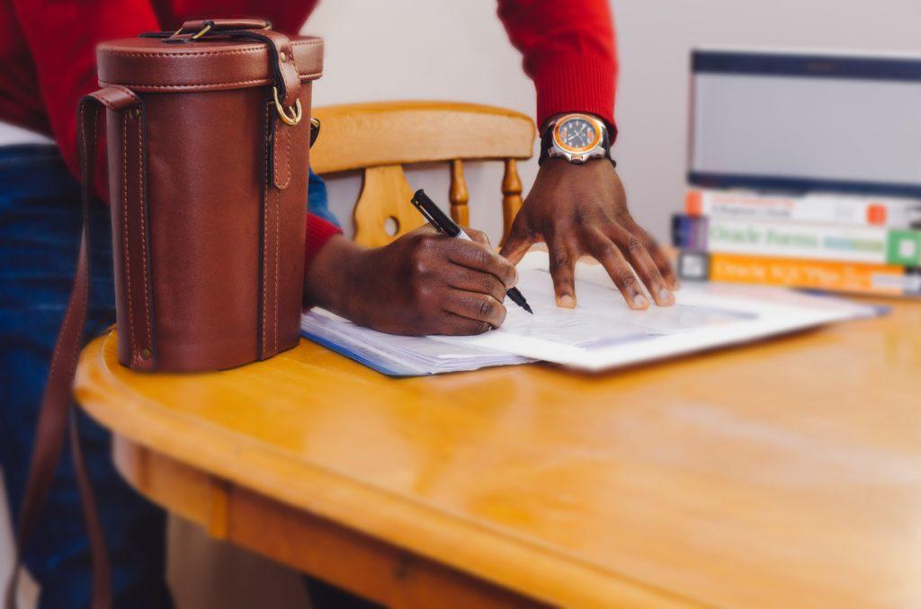 homem assinando documentos