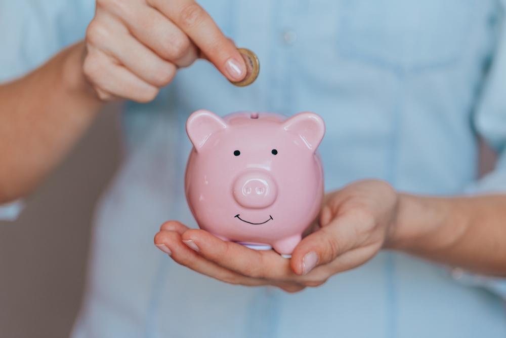 pessoa colocando moeda no porquinho de cofre