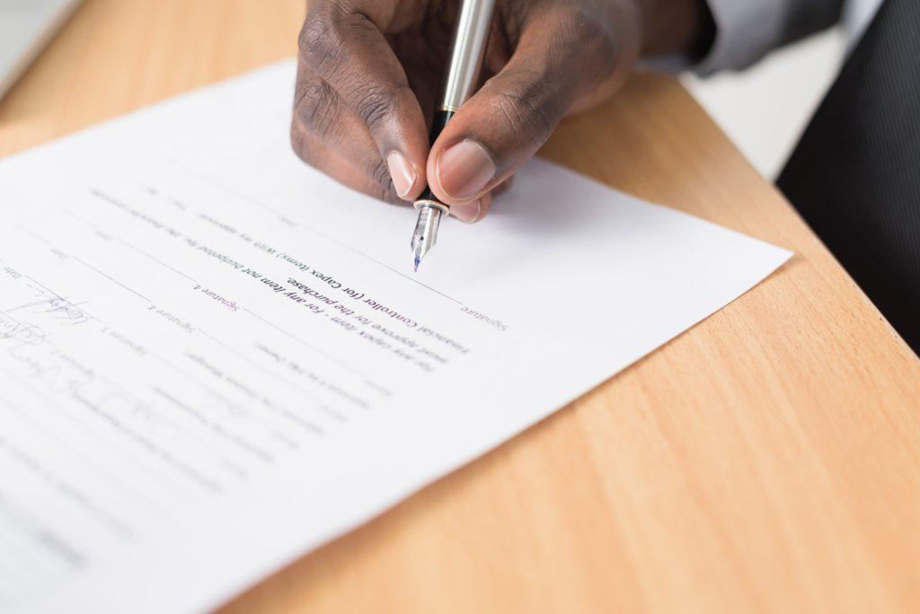 mão assinando documento (franquias de comida)