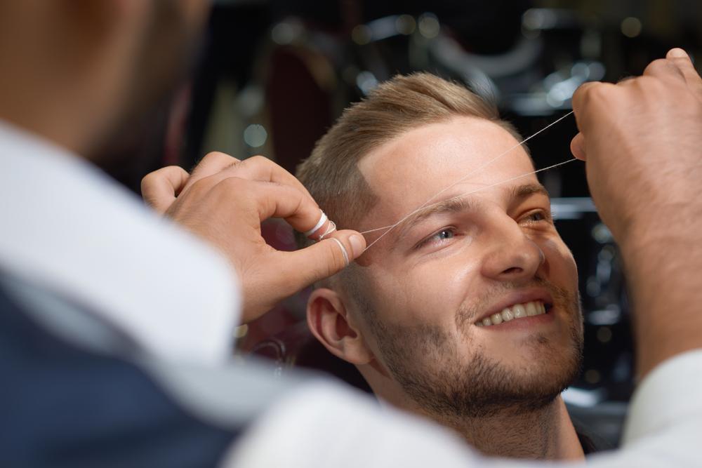 Homem passando pelo processo de desenho da sobrancelha