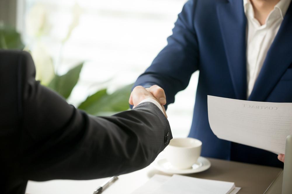 Homem firmando contrato com outro e homem