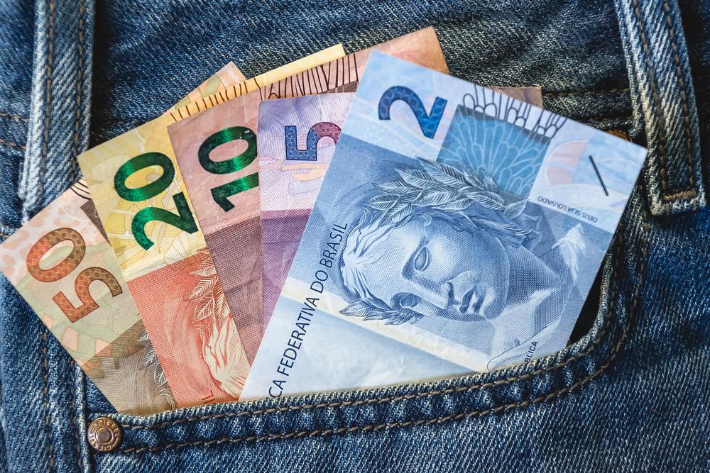 bolso com diversas notas de dinheiro em real
