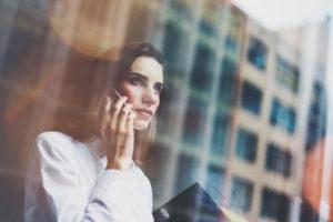 Mulher ao telefone olhando para o horizonte. Junto com o reflexo de prédios da sua janela