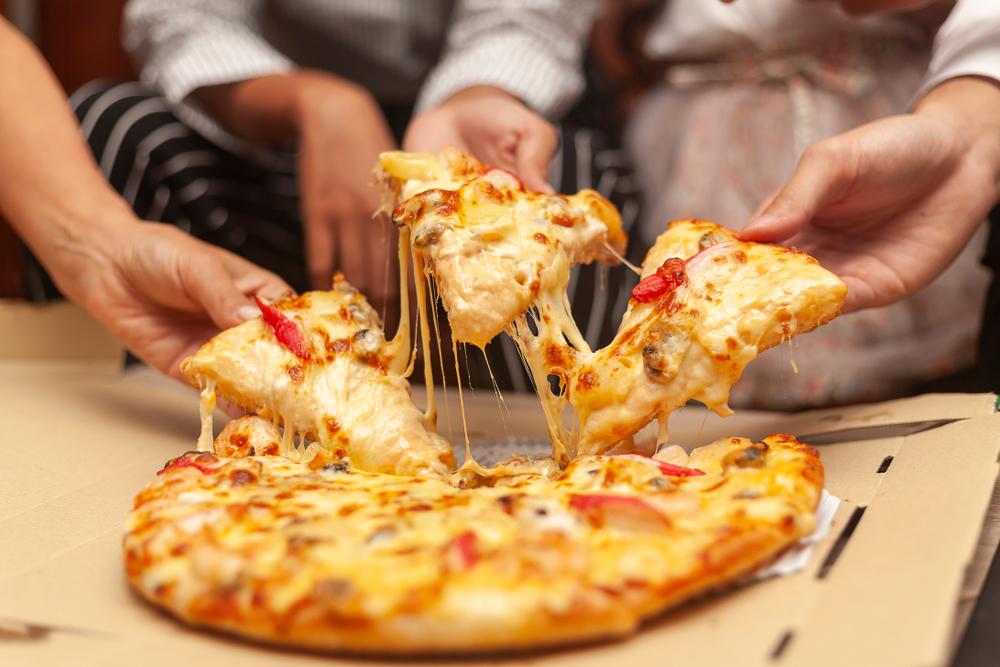 pessoas em volta da mesa compartilhando pedaços de pizza (franquias baratas no RJ)