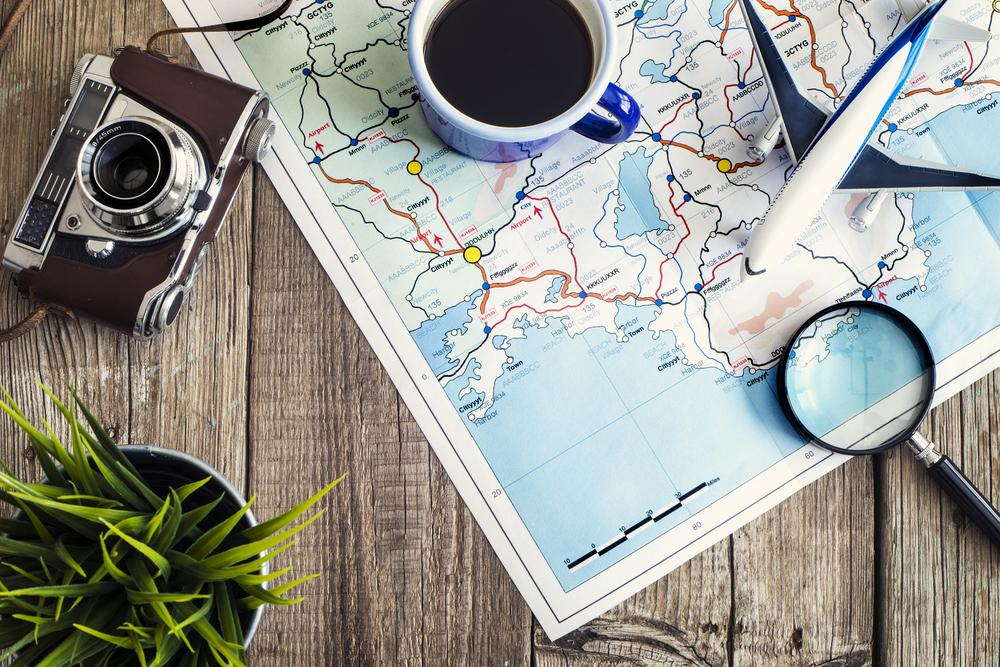 Franquais baratas 2021: mapa com uma xicara, avião em miniatura, lupa e camera fotográfica por cima