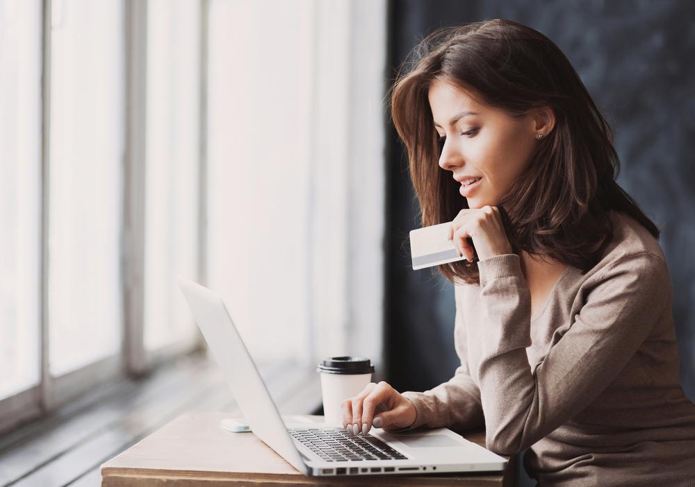 Franquias baratas 2021: mulher utilizando cartão para fazer pagamento em seu computador