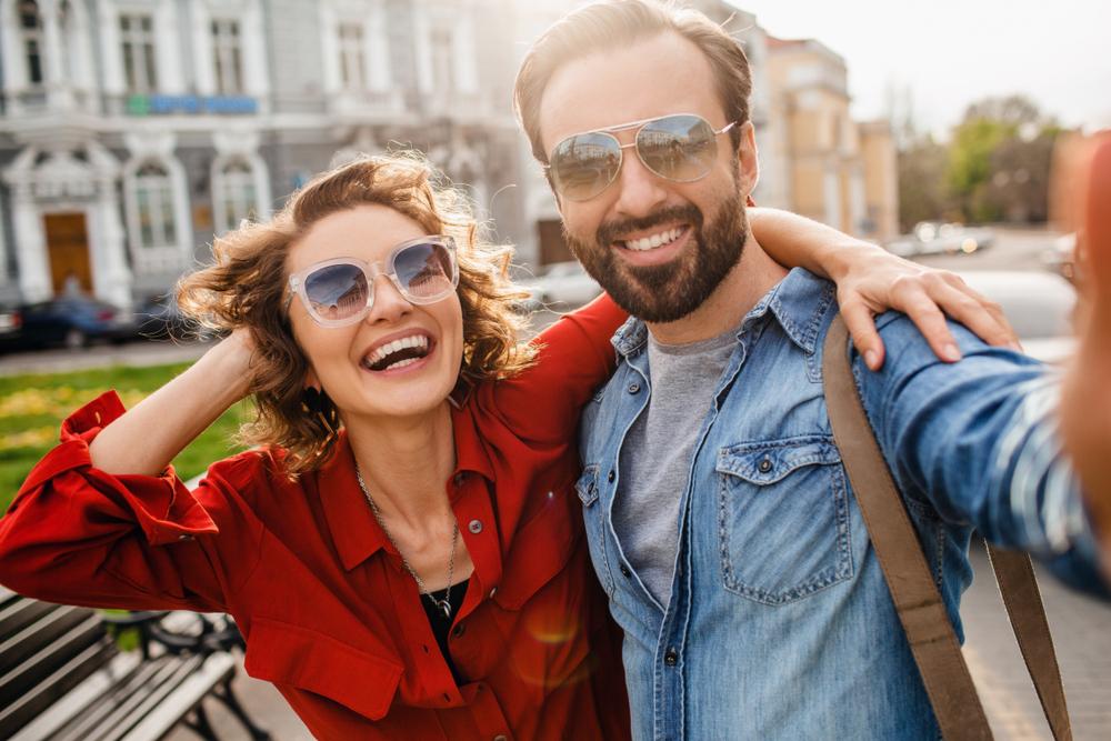 Casal tirando fotos em frente a um banco e usando óculos de sol