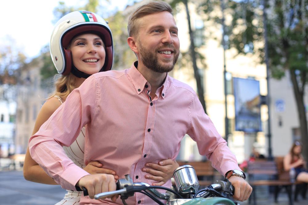 Casal andando de moto em uma cidade europeia