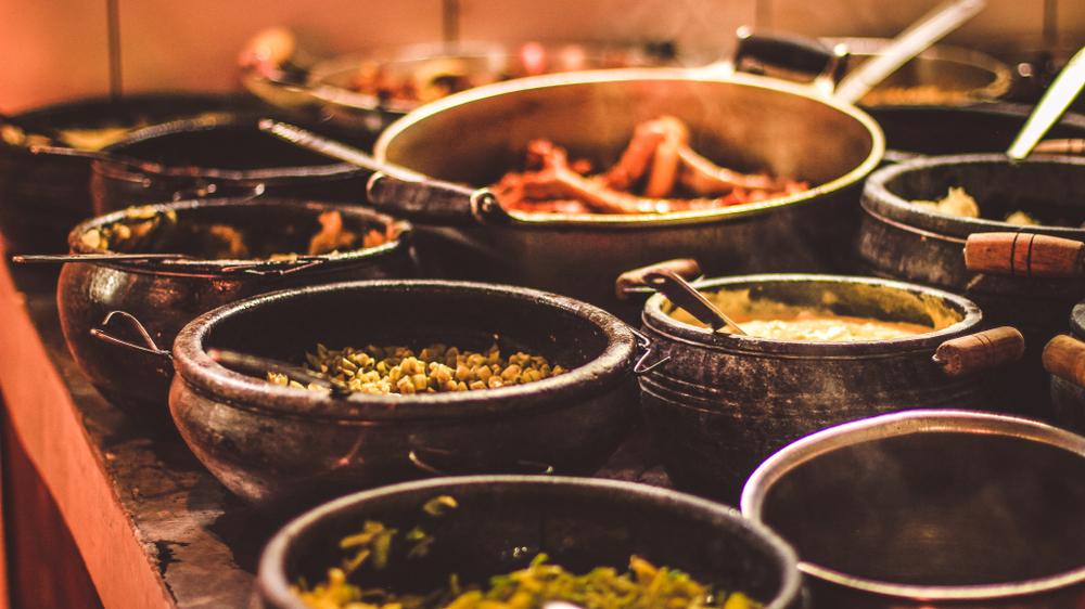 varias panelas de barro cheias de comidas típicas em um restaurante de comida mineira