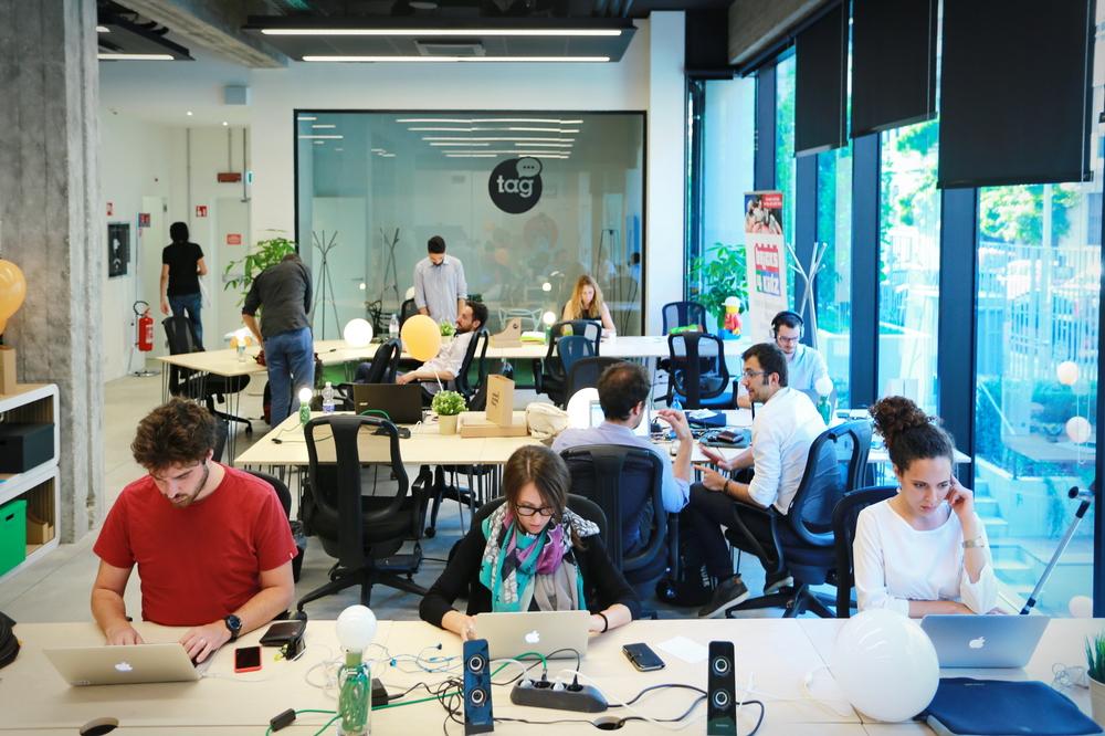 franquias baratas 2021: imagem de um coworking com profissionais atuando em seus computadores e em reunião