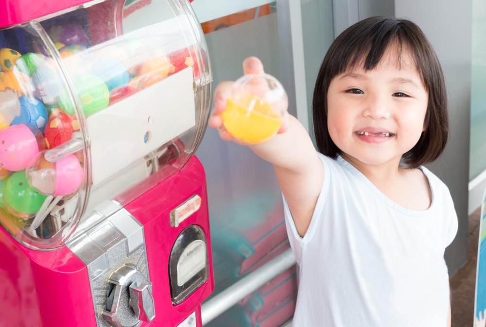 franquias baratas 2021: criança ao lado de uma máquina de brinquedos demonstrando a bolinha que ganhou