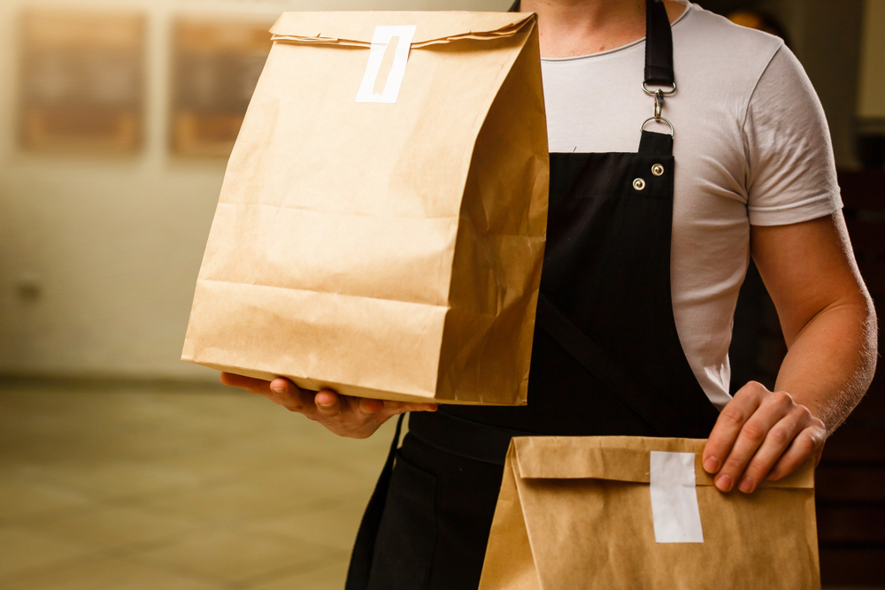 Franquias Baratas 2021: homem segurando sacos de entrega