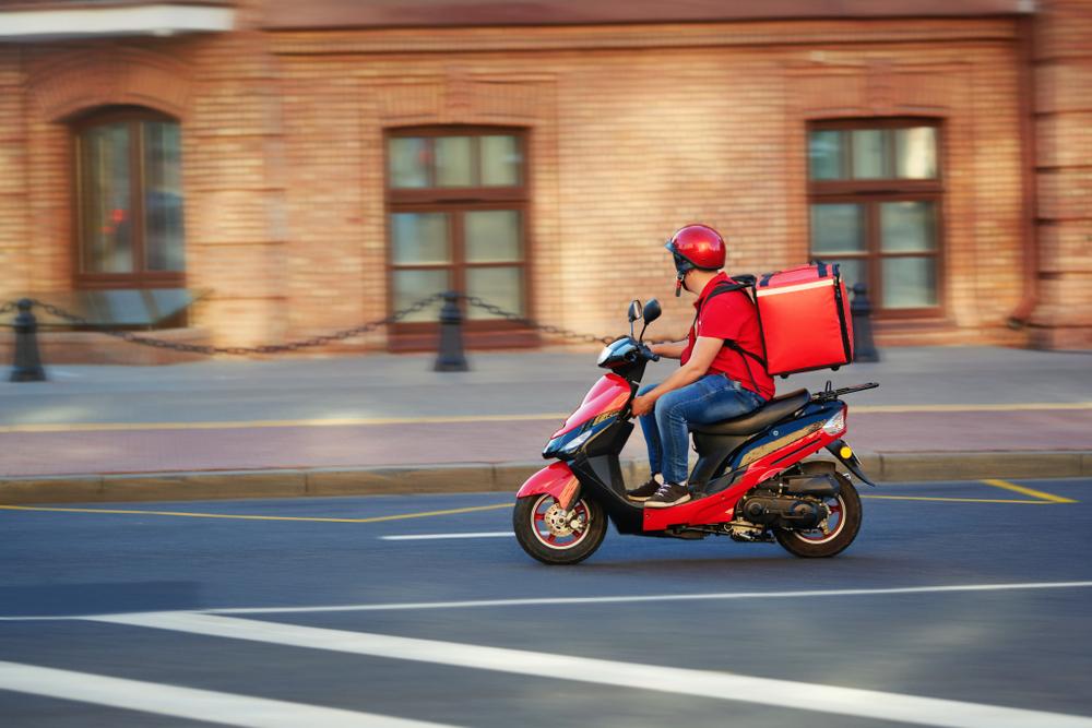 Franquias baratas 2021: entregador de delivery em sua moto em uma rua tranquila