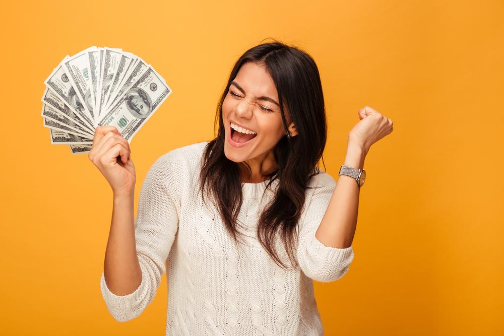 mulher segurando dinheiro e feliz
