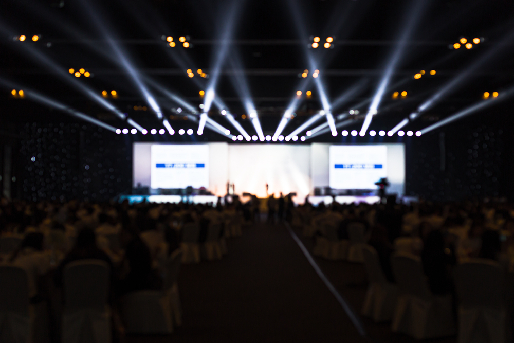 imagem de um evento com seu palco iluminado e as cadeiras das pessoas que estão acompanhando