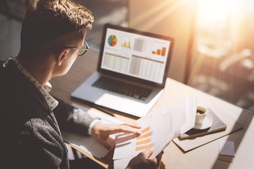 homem analisando gráfico em seu computador coe comparando com o que tem no papel.