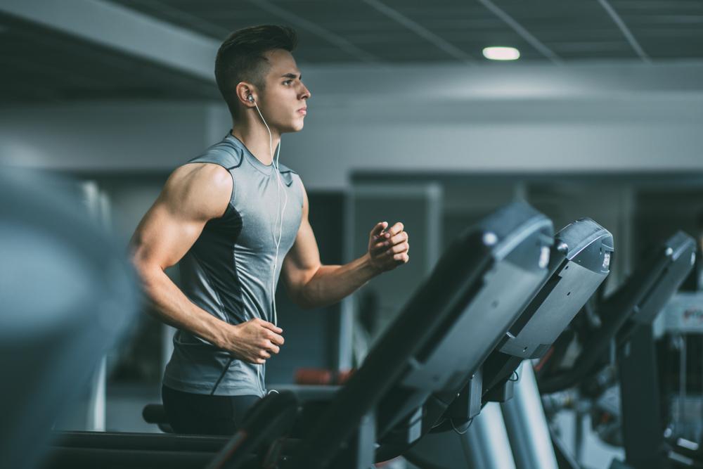 franquia de moda fitness: homem fazendo exercício na esteira ouvindo música com fone