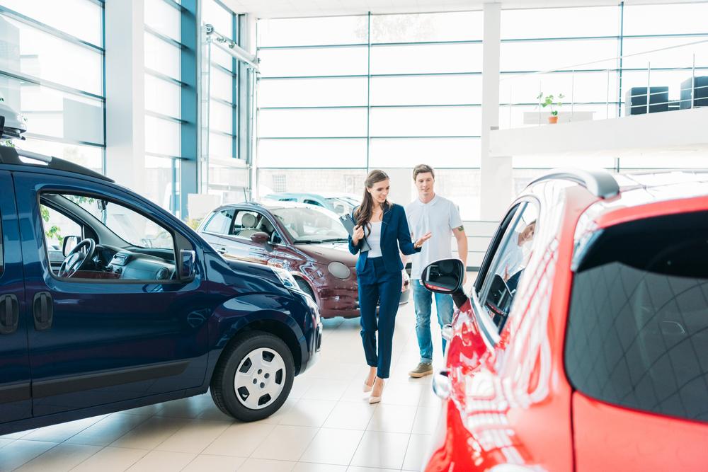 vendedora em  concessionária mostrando carros para cliente