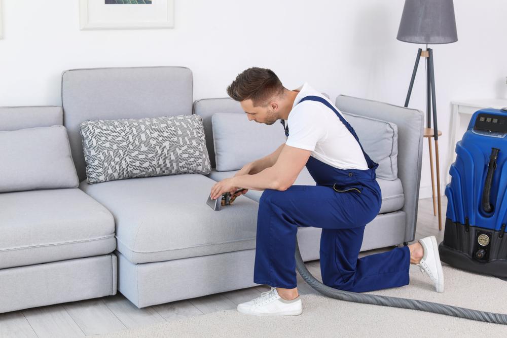 Homem fazendo a limpeza de um sofá com equipamento profissional