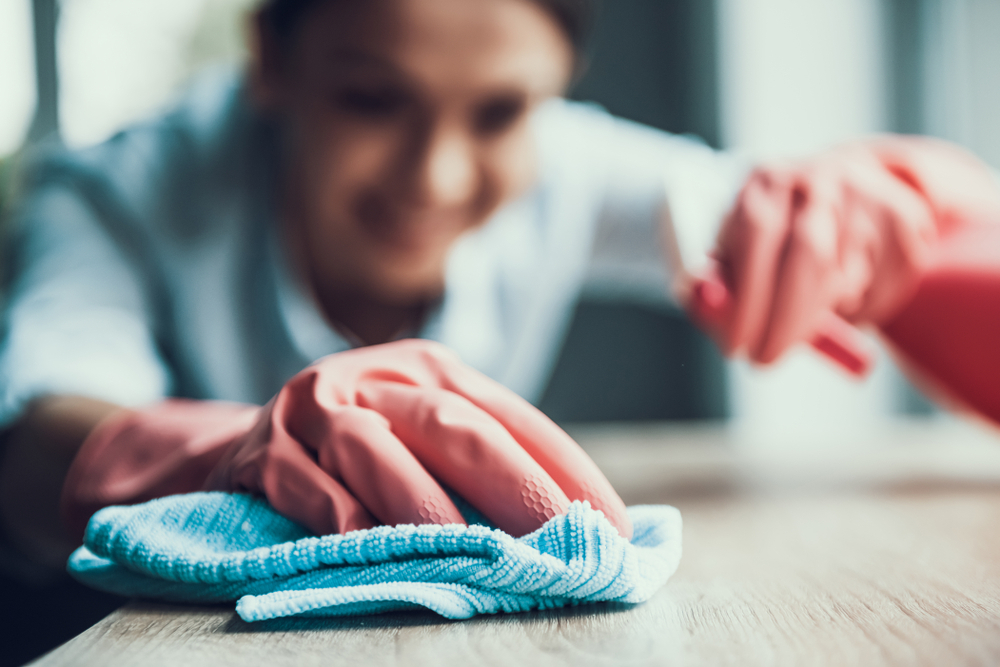 franquias baratas 2021: mulher fazendo limpeza de uma mesa com pano e borrifador