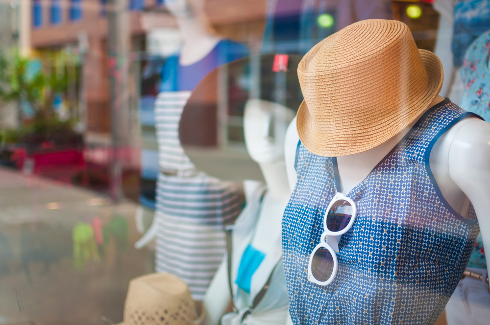 Franquias mais baratas: vitrine de uma loja de roupas de verão femininas. Detalhes em azul e laranja