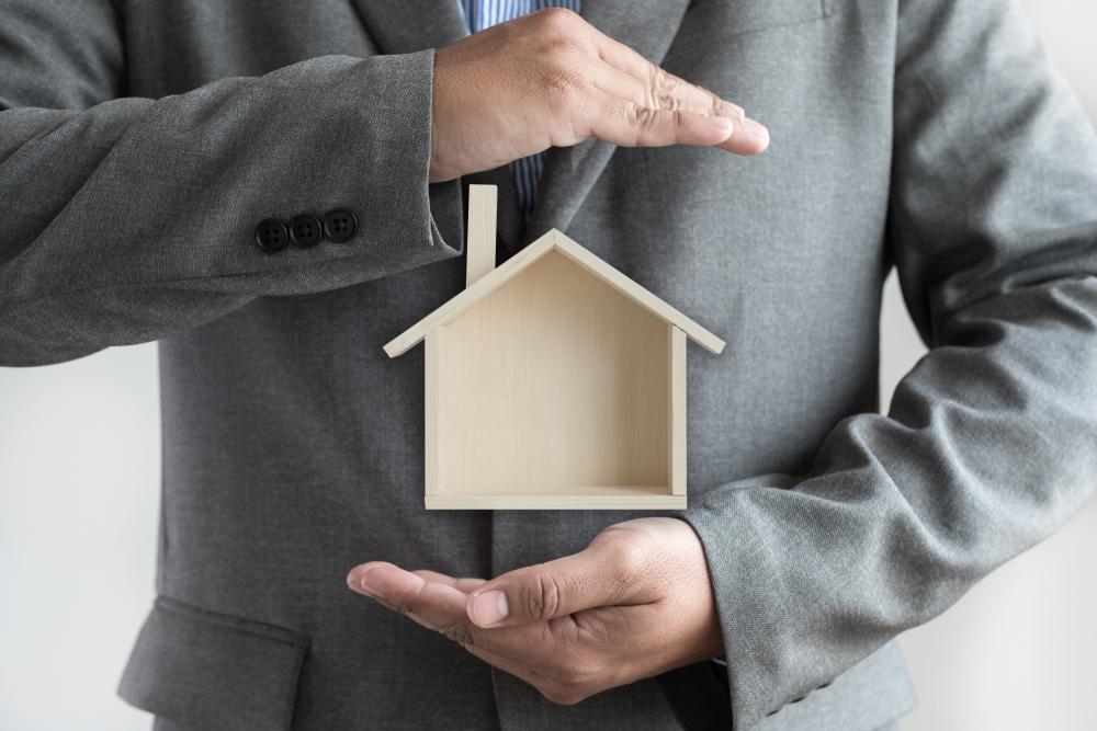 Franquias baratas 2021: homem de terno protegendo uma casa de madeira com suas mãos