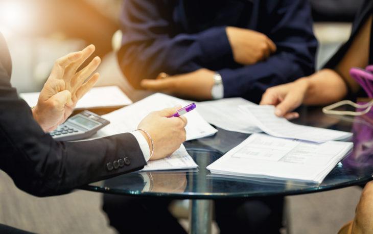 reunião em mesa redonda mãos analisando papeis (franquias mais procuradas)