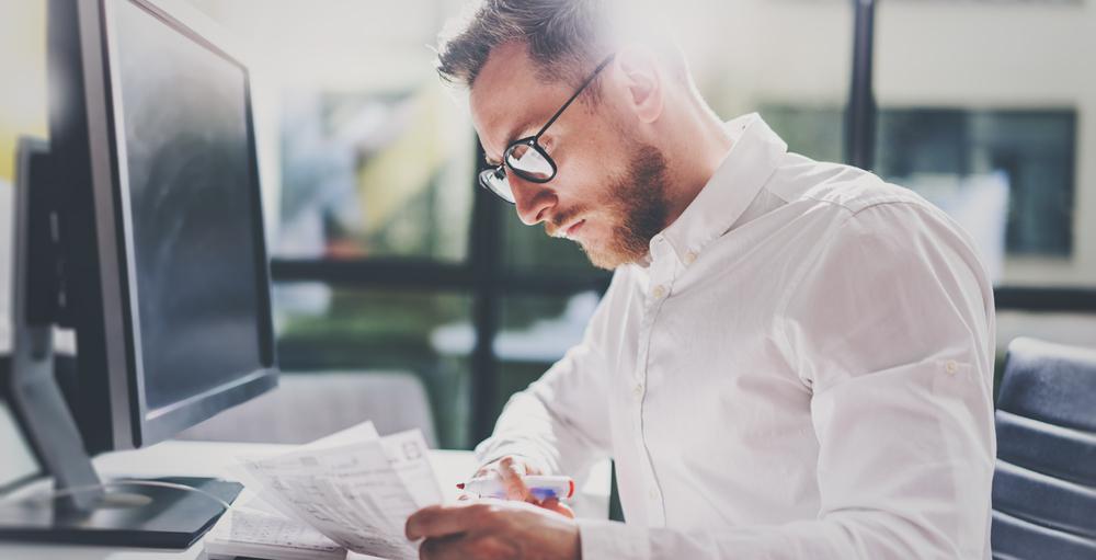 Homem sentado em frente a um computador analisando documentos e marcando com uma caneta vermelha