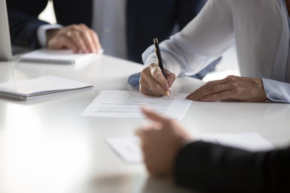 franquias baratas 2021: homem assinando contrato com dois empresários ao fundo
