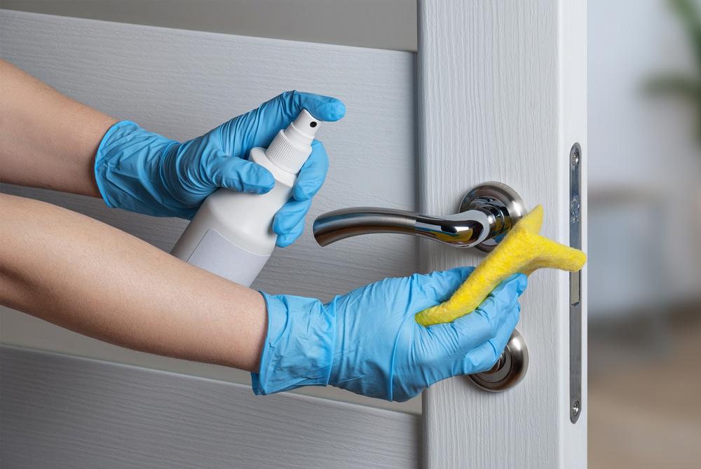 pessoa limpando a fechadura de uma porta com pano e borrifador com produto especial para dar brilho