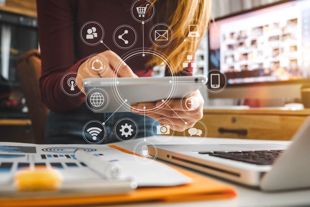 franquias baratas 2021: mulher com tablet e computador e desenhos relacionados com marketing digital