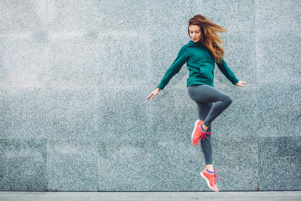 franquia de moda fitness: mulher com roupa fitness em uma calçada fazendo exercício