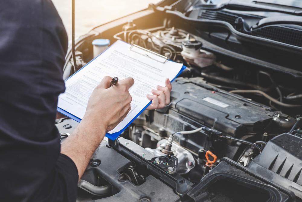 Franquia de oficina mecânica: mecânico preenchendo formulário de entrada de um carro. Analisando o motor