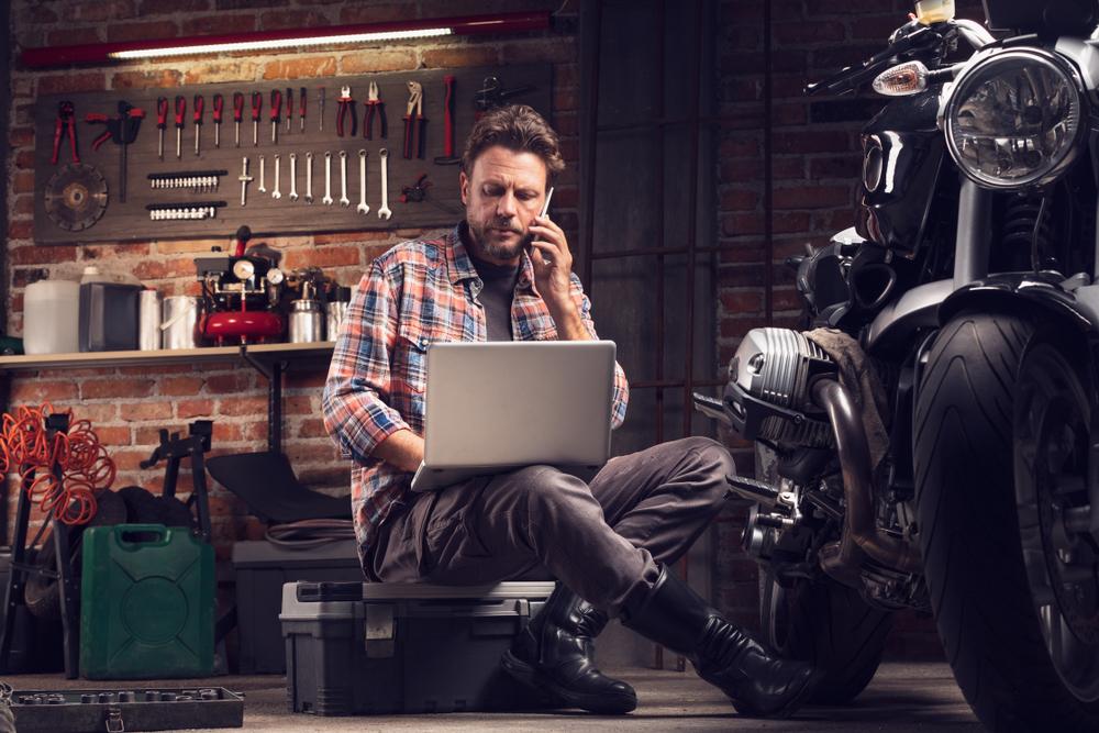 Franquia de moto peças: homem olhando computador, conversando no celular, em sua oficina e um moto ao lado