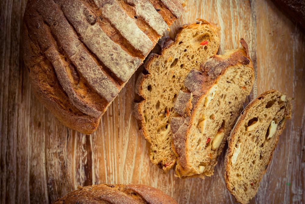 pão artesanal de recheado com pedaços de queijos e tomate.
