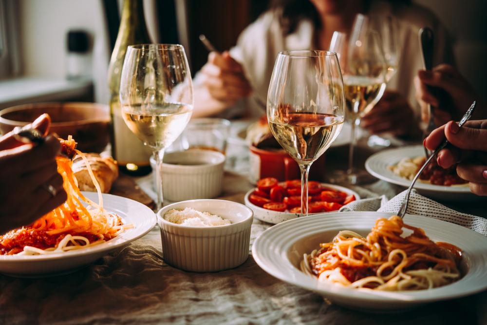 franquia de restaurante: mesa com três pessoas comendo macarrão e algumas taças de vinho