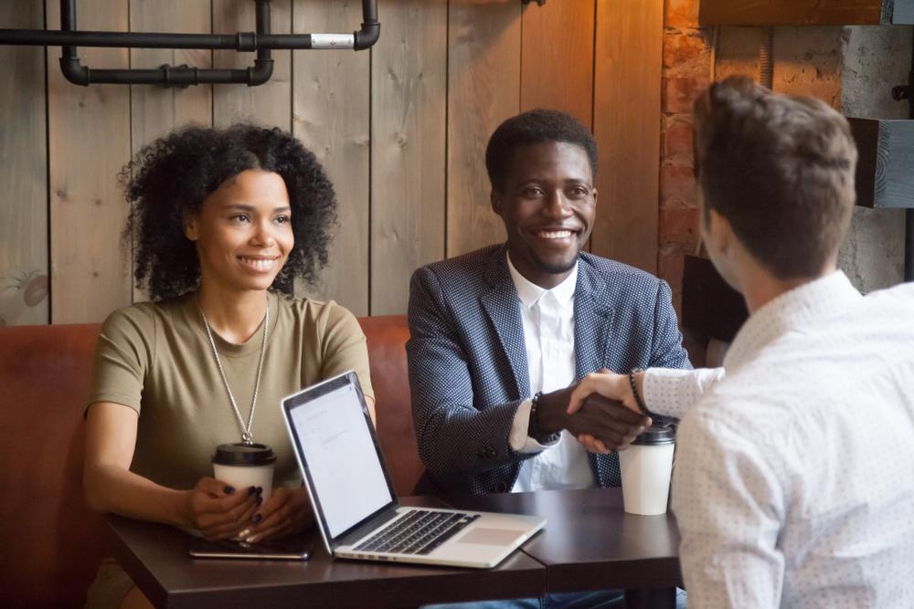 Casal apertando a mão de outra pessoa em uma cafeteria após fechar um acordo