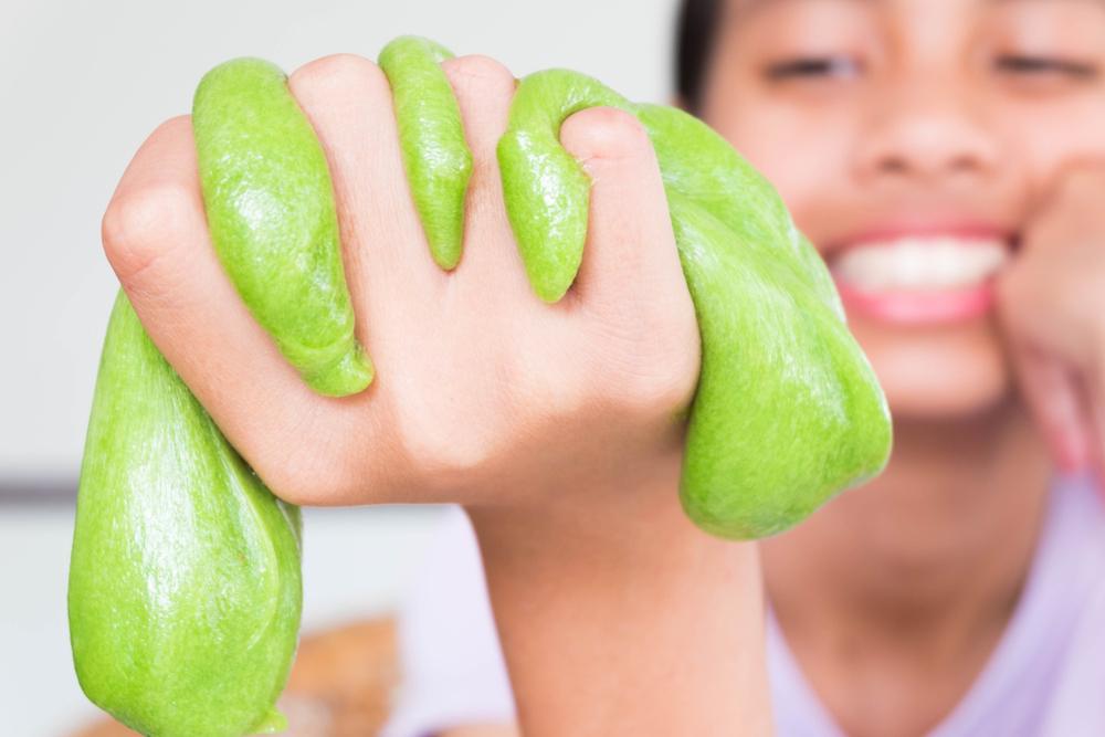 Criança segurando um slime verde