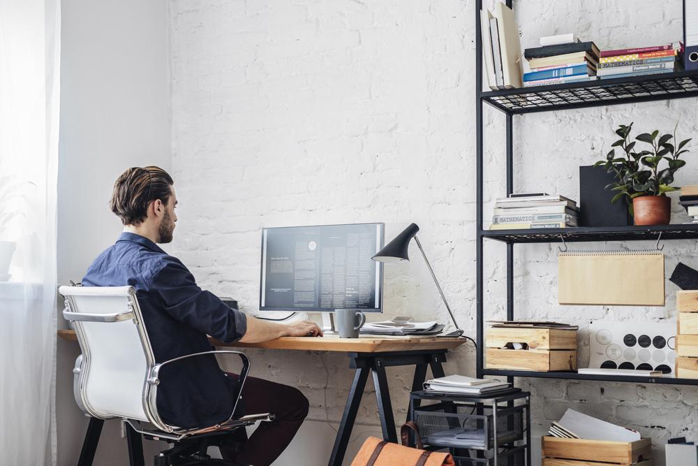Franquia de oficina mecânica: Homem sentado em seu escritório pessoal, ao lado de uma estande de livros e estudando em sua mesa com computador