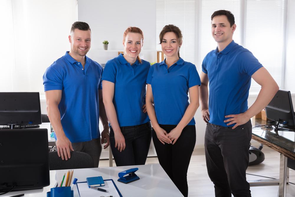 Franquias baratas 2021: funcionários de uma empresa posando com uniforme azul