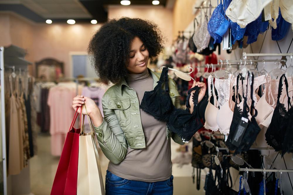 mulher com três lingeries em suas mãos, como se estivesse em dúvida de qual escolher