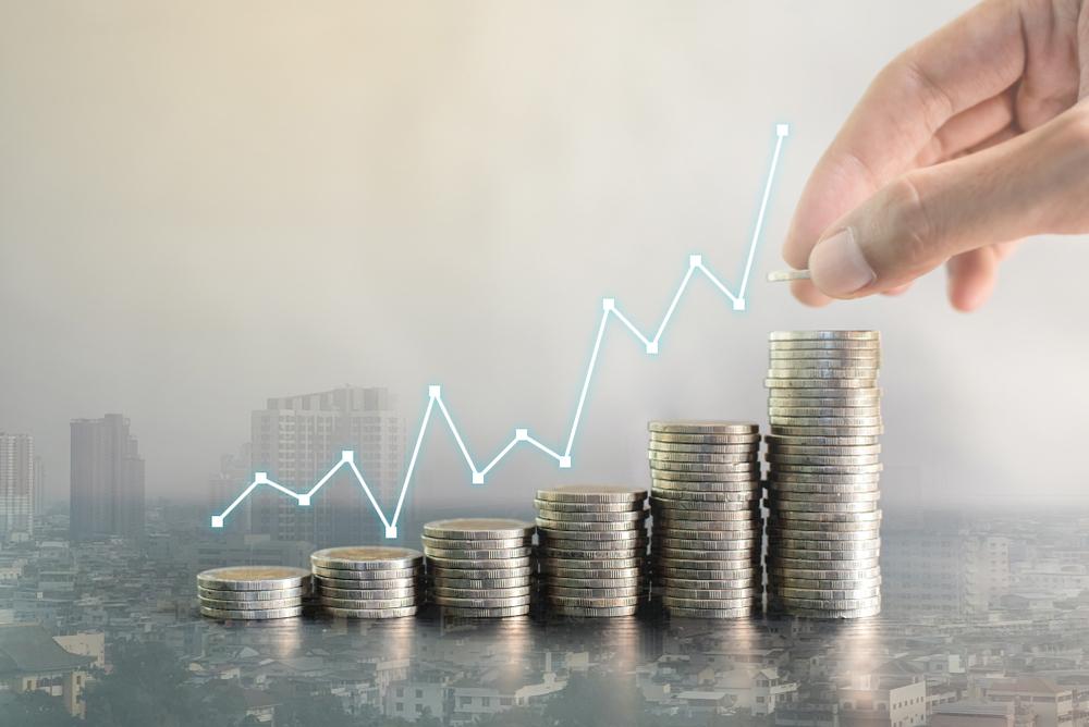 Como abrir uma franquia: pilhas de moedas em escadinha mostrando o crescimento de um empreendimento. Linha de gráfica acompanhando o as moedas