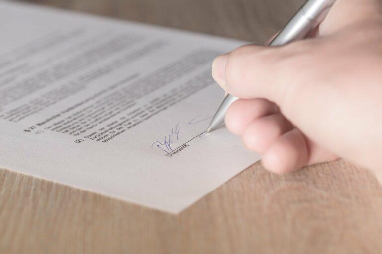 Foto da mão de uma pessoa assinando um contrato em uma mesa de madeira. Imagem ilustrativa para texto pré-contrato de franquia.