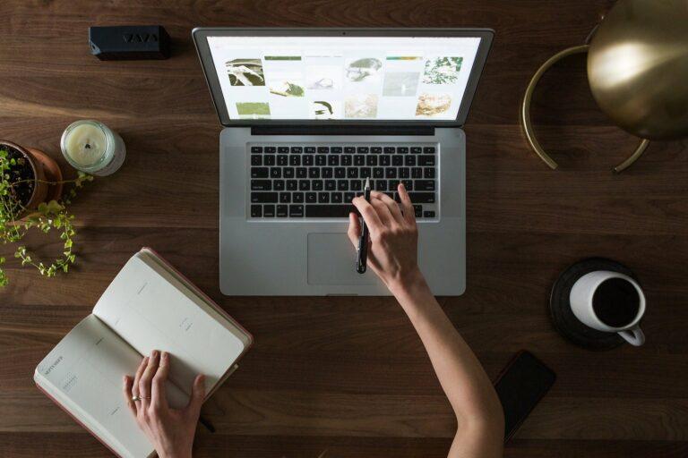 Foto de uma pessoa usando um computador em uma mesa de madeira, vemos também uma planta, xícara e caderno ao lado. Imagem ilustrativa para texto franchising e licenciamento.