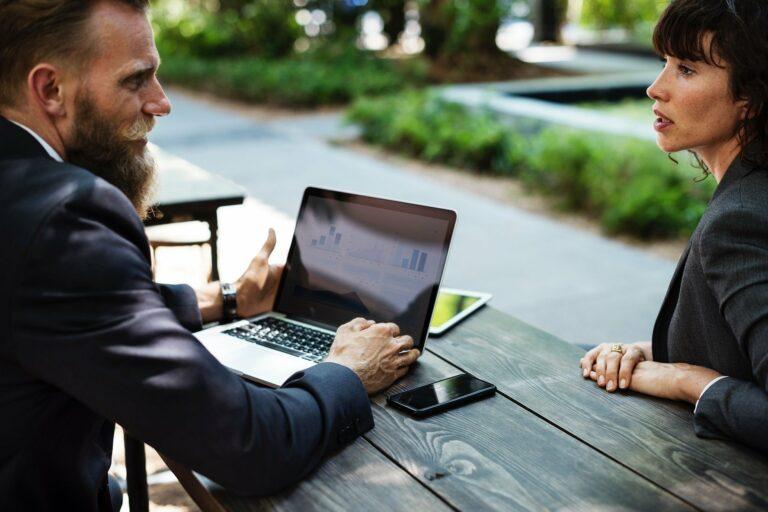 duas pessoas de roupas pretas em uma mesa no parque com computador e celular, conversando. imagem ilustrativa para texto franqueado e o franqueador.