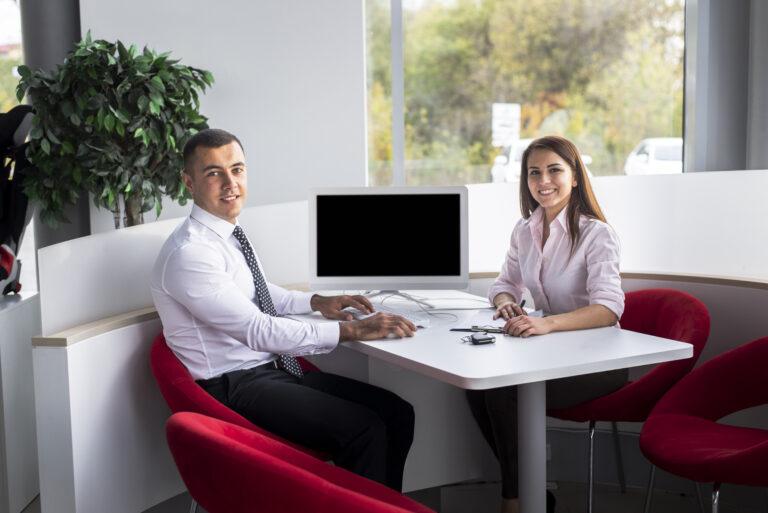 Imagem de duas pessoas sentadas em uma mesa fechando um negócio.